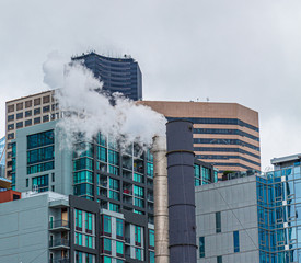 Wall Mural - Steam from Smokestack in front of modern buildings in Seattle