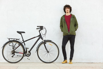 Pleased active young hipster being in riding tour, having stop to relax, standing near his bicycle, keeping his hands in pockets, being sport amateur, looking calm. Leisure time activities concept.