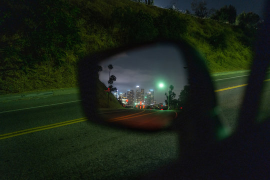 Los Angeles downtown skyline at night reflected in side car mirror