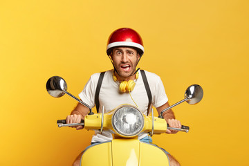Displeased handsome male driver drives on scooter, has puzzled facial expression, wears helmet, headphones around neck, reaches destination quickly, isolated on yellow background. Transport.