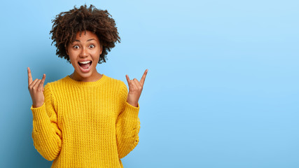 Excited lively energized curly woman makes heavy metal gesture, enjoys cool concert of favourite band, wears yellow knitted jumper, models on blue wall, blank space for your promotional contest
