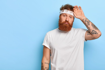 Fatigue sportsman wipes sweat on forehead, has unhappy look, wears white headband, has tattooed arms, had active training, leads healhthy lifestyle, stands over blue wall, blank free space on left Wall mural