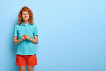 Unsure perplexed girl with wavy foxy hair, healthy skin, purses lips, focused away, wears casual t shirt and shorts, makes dicision, isolated on blue wall with empty space for your advertising content