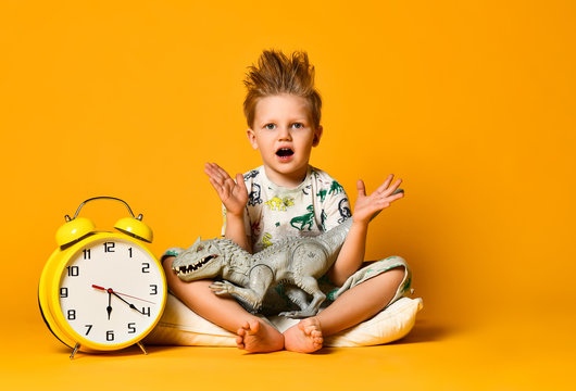 Little cute boy in pajamas holding a toy dinosaur in his hands, sitting on a pillow with an alarm clock. Isolated on a yellow background.