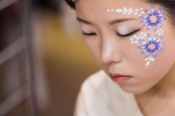Chiba, Japan, 02/18/2019 , Japanese young model with facepaint preparing for a photo shoot.