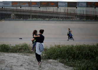 Migrant women with their children cross illegally into El Paso, Texas, U.S. as seen from Ciudad Juarez