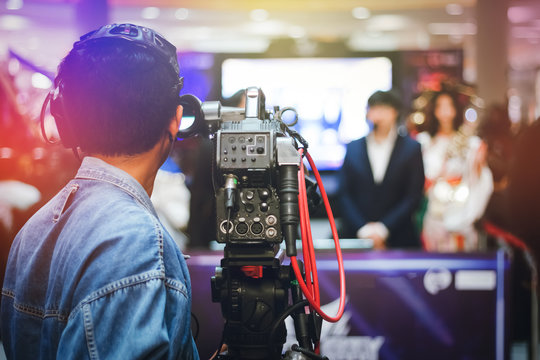 Video camera operator using camcorder to record indoor event