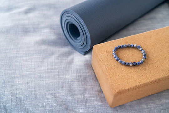 Yoga mat organic materials accessories for yoga - linen towel on floor, mala beaded bracelet for meditation beads counting on cork block next to rolled natural rubber mat.