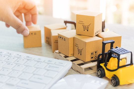 Mini forklift truck load cardboard boxes with symbols on wood pallet and fingers touch box and keyboard nearby. Logistics and transportation management ideas and Industry business commercial concept.