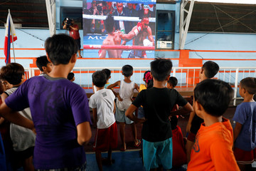 Filipino boxing fans watch the WBA Welterweight match between Philippine boxing icon Manny Pacquiao and Keith Thurman of the U.S. in a live public viewing in Marikina