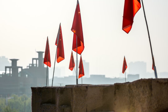 Chinese flags lining Kashgar's renovated Old City wall, with modern buildings in the background.  Kashgar, Xinjiang, China.