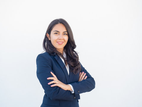 Happy confident female business leader posing in studio background. Beautiful young Latin woman in formal suit standing with arms folded and smiling at camera. Successful businesswoman concept