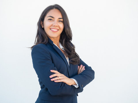 Smiling confident businesswoman posing with arms folded. Happy beautiful black haired young Latin woman in formal suit standing for camera over white studio background. Corporate portrait concept