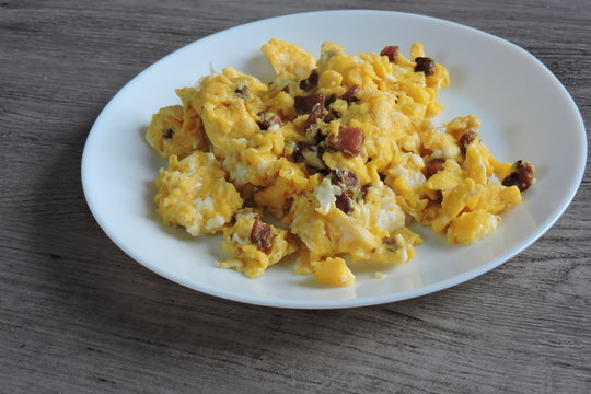 Scrambled eggs with fried bacon and sausage served on a white plate, gray plank in the background