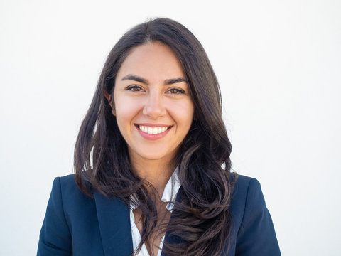 Happy successful businesswoman smiling at camera over white studio background. Closeup of beautiful black haired young Latin woman wearing formal jacket and smiling. Business portrait concept
