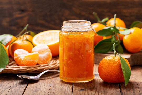 glass jar of orange tangerine or mandarin jam with fresh fruits