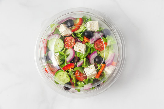 Healthy greek salad in plastic package for take away or food delivery on a white marble background