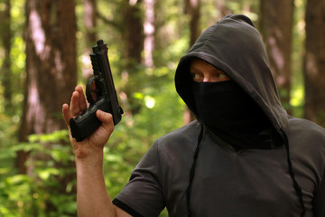 Man in hood with the pistol in the forest.