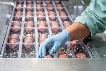 Workwoman preparing sausages in red casings for storaging. Sausage production line. Sausage production line in modern meat factory.