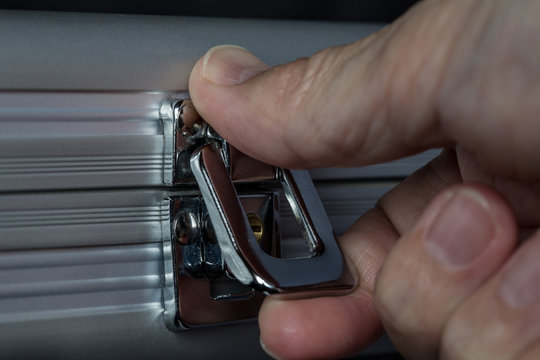 Extreme close-up of human hand opening or closing metal briefcase