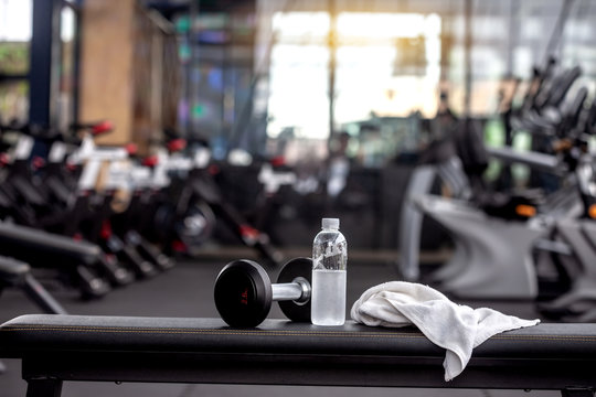 Dumbbell, water bottle, towel on the bench in the gym.