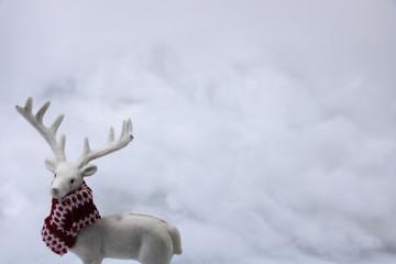 ressource graphique avec espace texte, cerf blanc avec une écharpe aux couleurs de noël dans un décor blanc de neige, pour les fêtes de noël, de fin d'année et pour la saison d'hiver