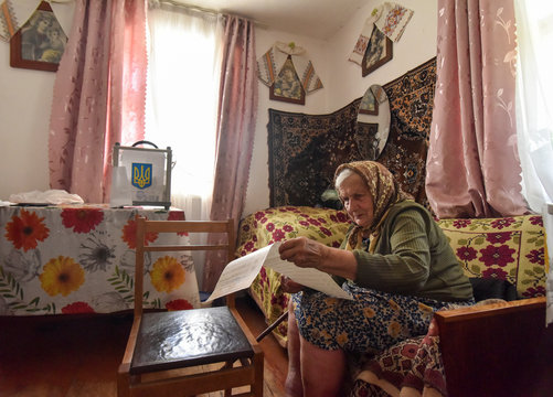 Local resident studies her ballot at home during a parliamentary election in the village of Krekhiv in Lviv region