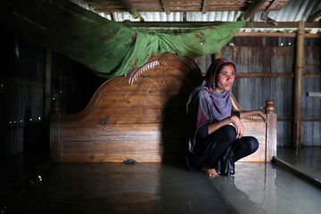 Shilpi, a flood-affected woman poses for a picture inside her flooded house in Jamalpur