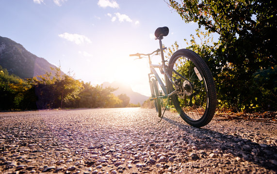 Healthy lifestyle. Close up of mountain bicycle on the road against sunny sky.