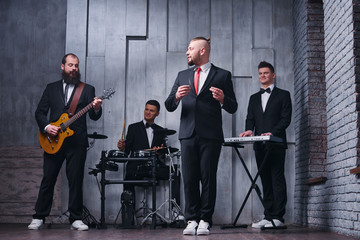 Music band and fashion.  Handsome young men in suits playing rock and singing song.