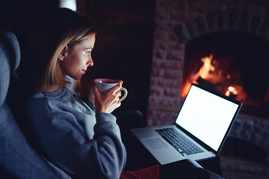 Cozy home. Pretty young woman working on laptop computer near the fireplace. Copy space on the screen.