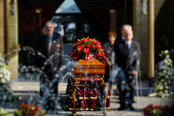Blurred image of family standing by a coffin at a funeral