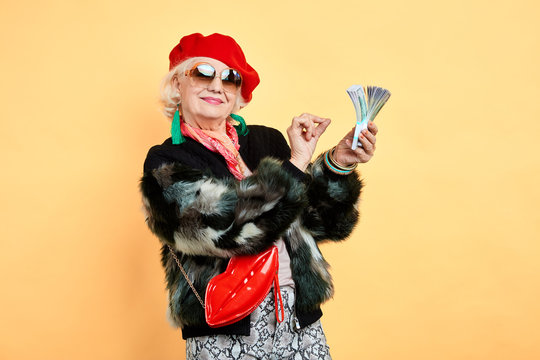 Happy aged woman holding money, counting it, Emotion and feelings concept.old businesswoman holding much money, happiness,prosperous business, isolated yellow background. studio shot