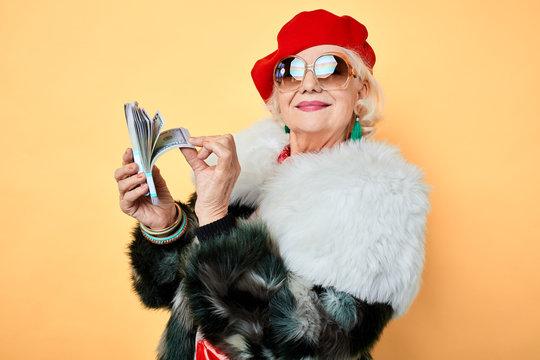 happy old stylish woman in sunglasses boasting her money. isolated yellow background, studio shot, fashion, style