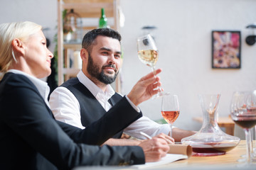 Young successful cavist looking at white wine held by his colleague