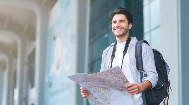 Tourist man looking for route on map at airport