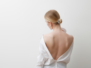 Minimalist photo, Fashionable girl in stylish summer things - white shirt. View from the back. Earrings, a ring . Street fashion , blogger style . Beauty . Minimalist Fashion clothes Wall mural
