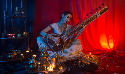 Beautiful young indian woman in traditional Sari clothing with Oriental Jewelry Playing the Sitar.
