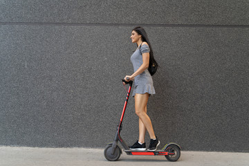 Side view beautiful long hair girl riding electric scooter, black wall background  Wall mural