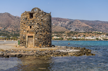 Ancient ruins of windmill and port in Elounda town, Crete island, Greece