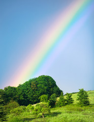 Rainbow over green hill meadow, summer landscape