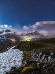Moonlit scene with illuminated green tent under starry night - fog rolling over mountains