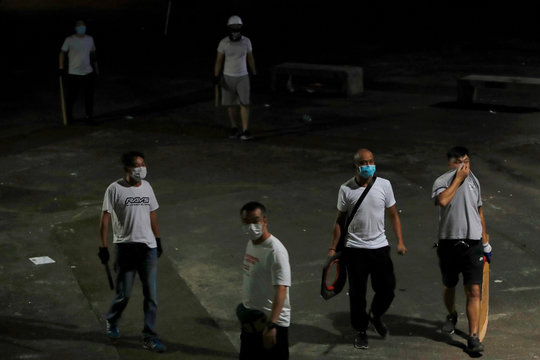 Men in white T-shirts with poles are seen in Yuen Long after attacking anti-extradition bill demonstrators at a train station, in Hong Kong