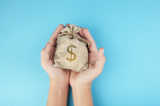 Women hold a money bag on blue background, Saving money for future investment concept.