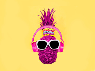 Pineapple in pink headphones and glasses on a yellow background