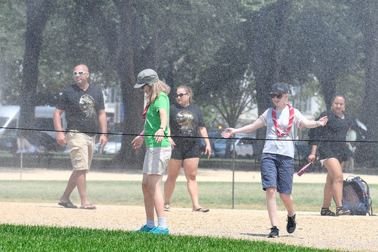 Tourists attempt to cool off with spray from a water sprinkler on the National Mall during heat wave in Washington,DC