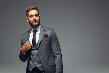 Stylish young man in suit and tie. Business style. Fashionable image. Office worker. Sexy man standing and looking at the camera