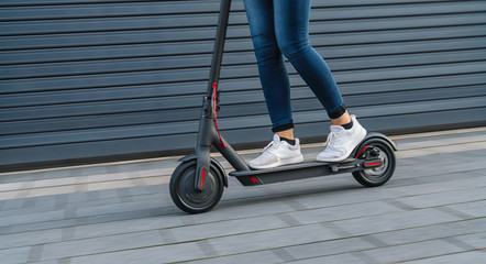 Close up of woman riding black electric kick scooter at cityscape, motion blur