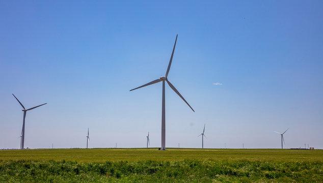 Wind turbines, renewable energy on a green field, spring day. Wind farm, West Texas, USA.