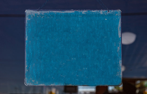Blank blue sign on a store entrance. Vintage metal plate, space for text.